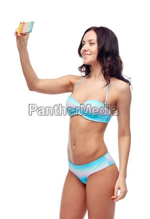 woman in swimsuit taking selfie with