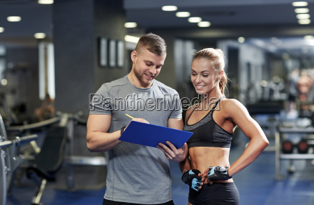smiling young woman with personal trainer