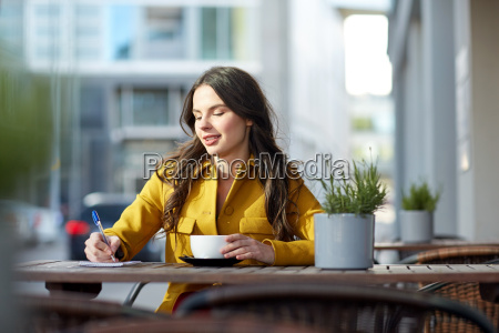 happy woman with notebook drinking cocoa