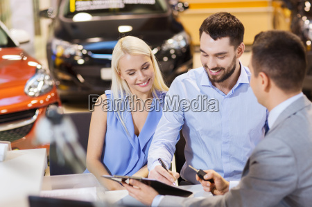 happy couple with car dealer in
