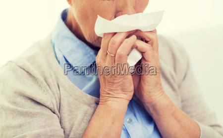 sick senior woman blowing nose to