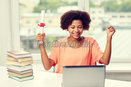 happy african woman with laptop books