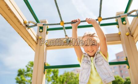 happy little girl climbing on children