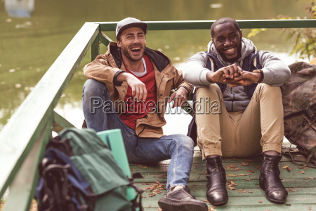 young, men, with, backpacks, sitting, on - 20114940