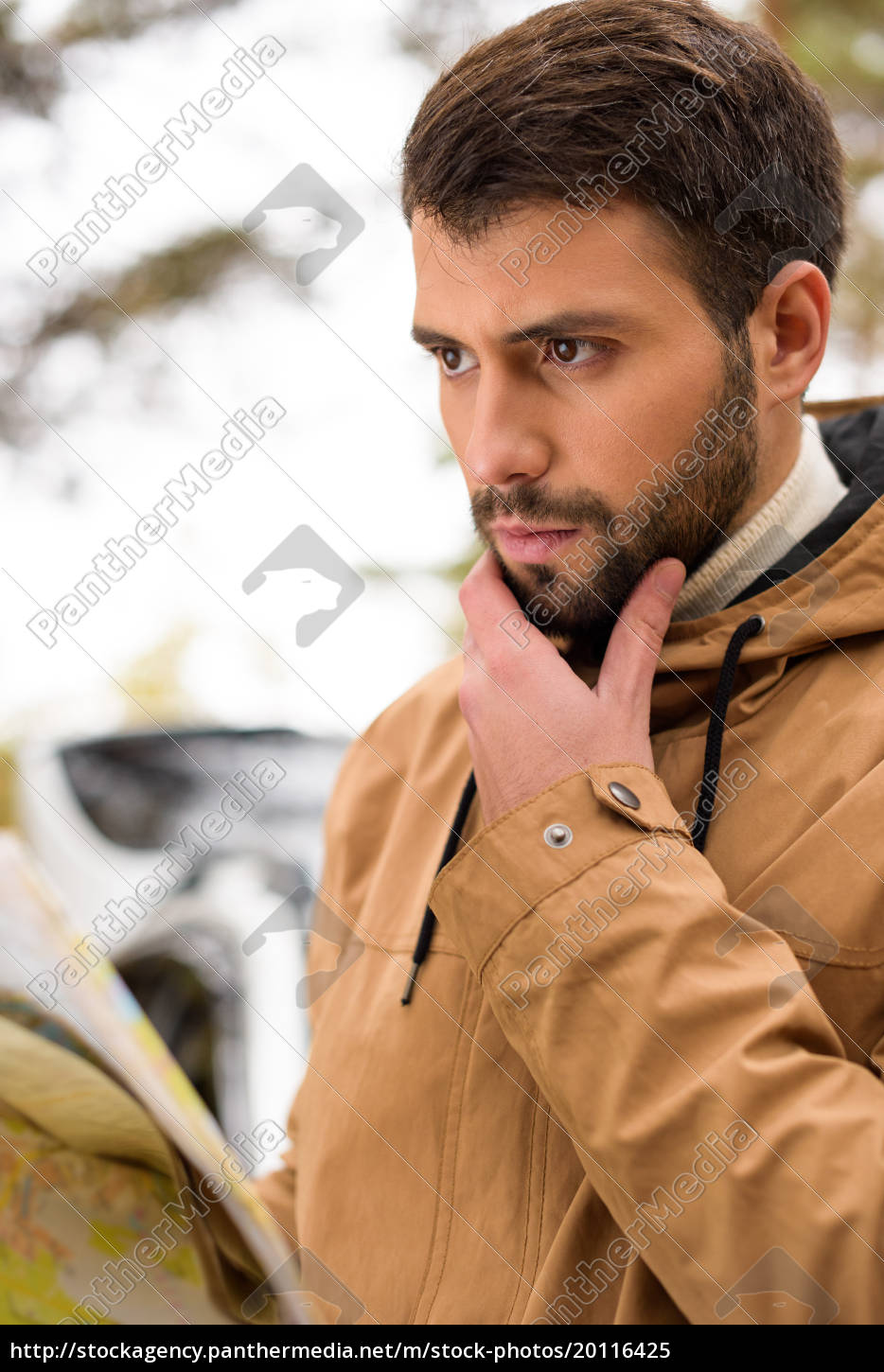bearded, man, holding, map, in, forest - 20116425