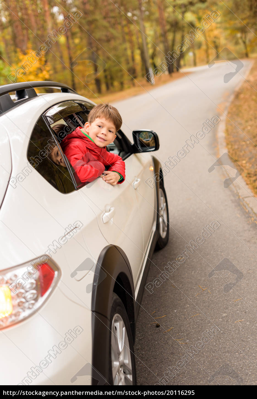 smiling, boy, looking, through, car, window - 20116295