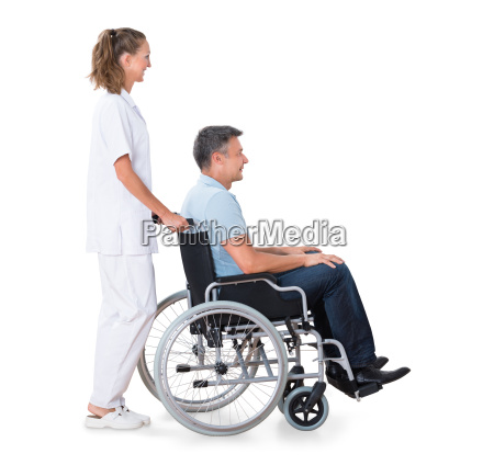 caretaker, pushing, disabled, patient, on, wheelchair - 20118835