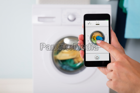 person, operating, washing, machine, using, cellphone - 20118865