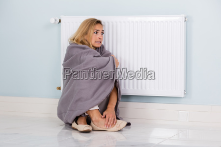 woman, in, blanket, sitting, near, thermostat - 20118773