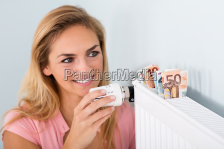 woman adjusting thermostat with bank notes
