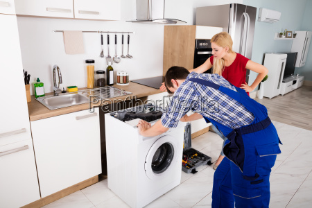 male worker repairing washer in kitchen