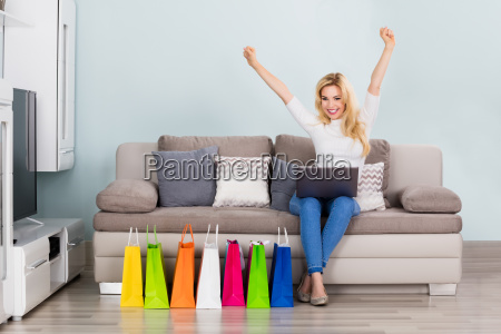 excited, woman, sitting, on, couch, with - 20119231