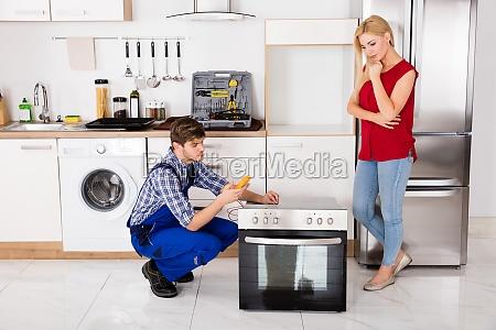 male, worker, repairing, oven, using, multimeter - 20119605