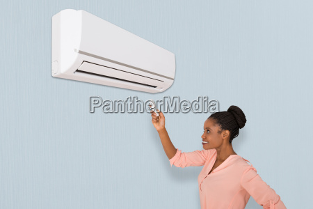 smiling, woman, operating, air, conditioner - 20119015