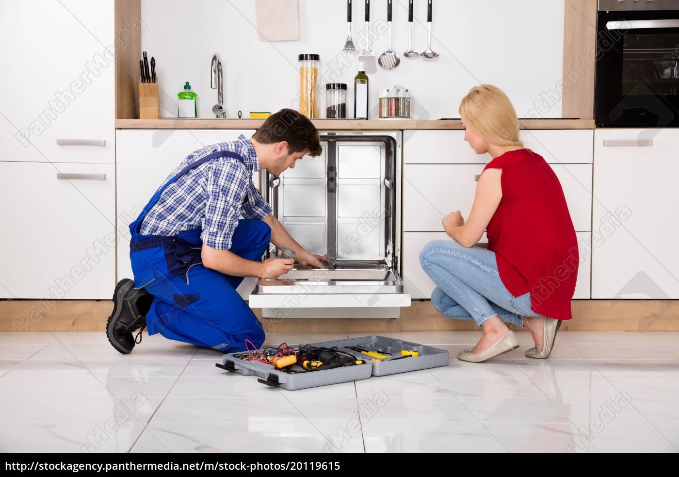 woman, looking, at, repairman, repairing, dishwasher - 20119615