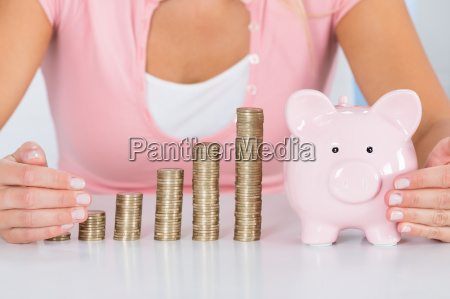 woman, protecting, piggybank, with, stack, of - 20119409