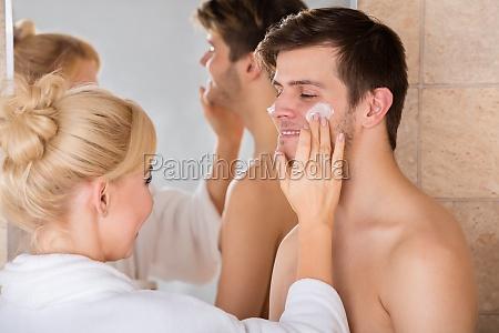 woman, putting, face, cream, on, man - 20119707