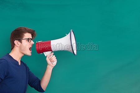 young, man, shouting, in, megaphone - 20119059
