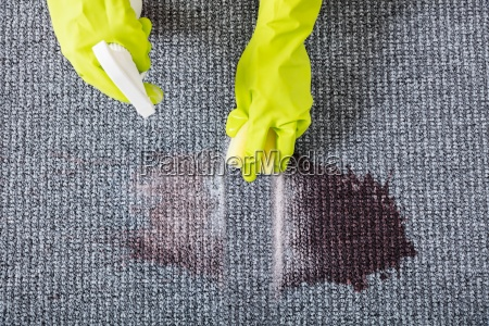 woman wiping stains on the carpet