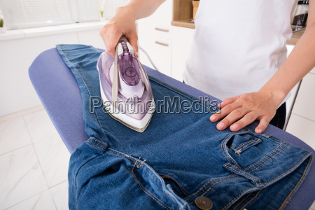 woman, ironing, jeans, on, ironing, board - 20125791