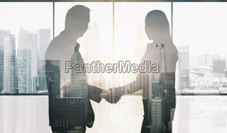 business partners silhouettes making handshake