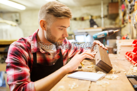 carpenter working with wood plank at
