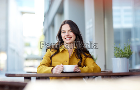 happy woman drinking cocoa at city