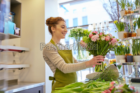 smiling florist woman making bunch at