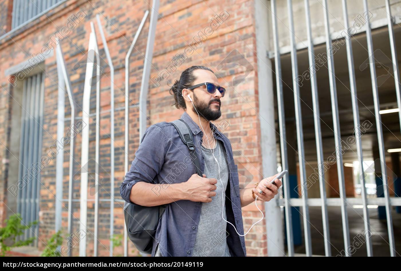 man, with, earphones, and, smartphone, walking - 20149119