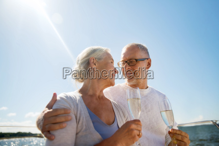 senior couple drinking champagne on sail