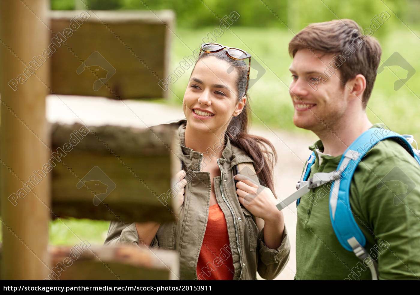 smiling, couple, at, signpost, with, backpacks - 20153911