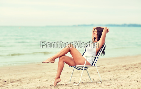 smiling, young, woman, sunbathing, in, lounge - 20154333
