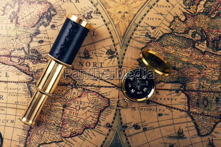 vintage compass and spyglass on ancient