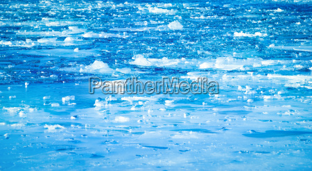 blue frozen river with small floes