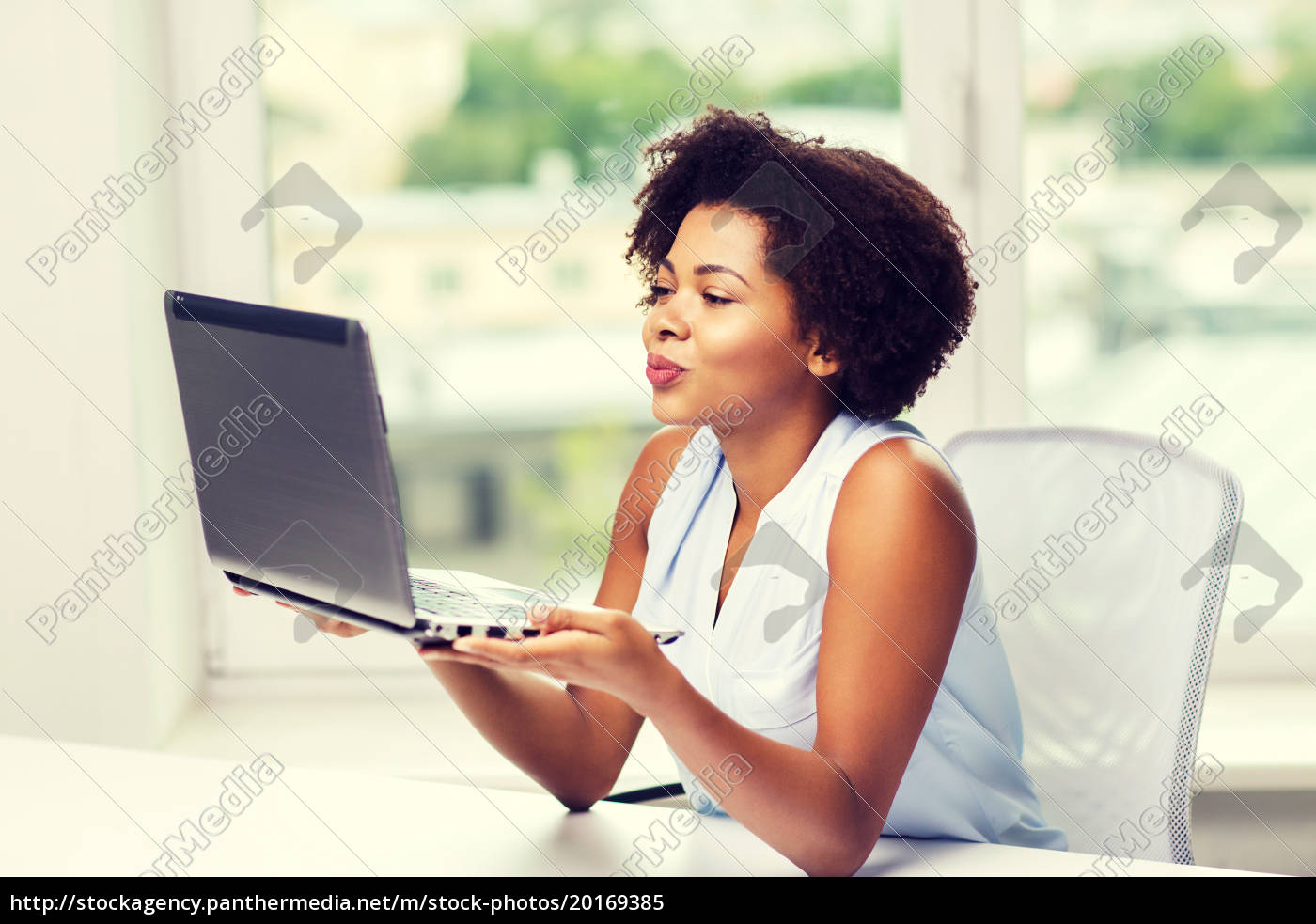 african, woman, sending, kiss, to, laptop - 20169385