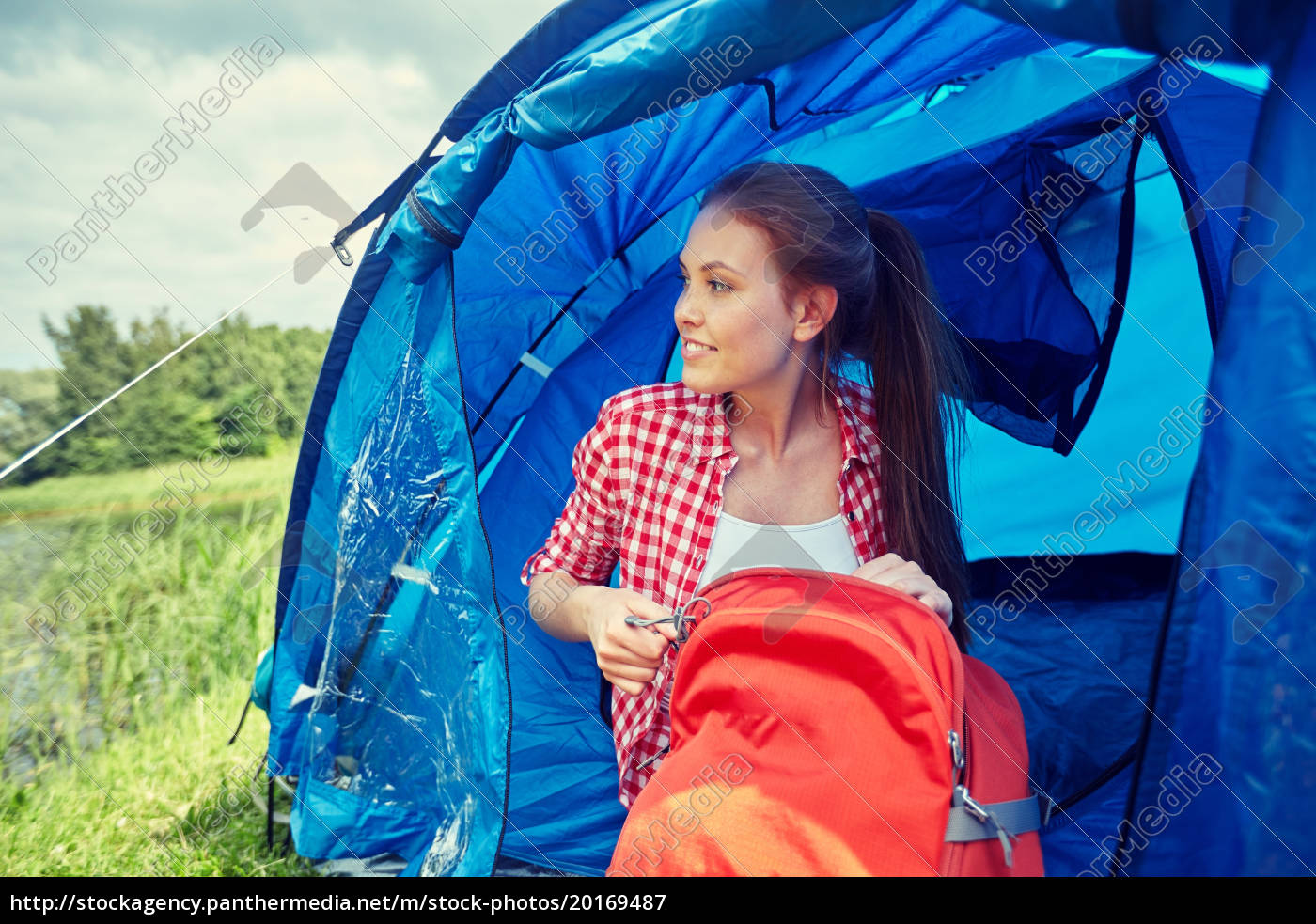 happy, young, woman, sitting, in, tent - 20169487