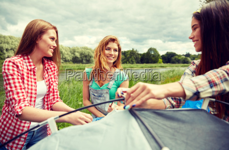 smiling, friends, setting, up, tent, outdoors - 20169959