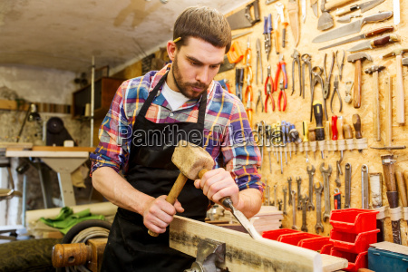 carpenter with wood hammer and chisel