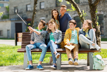 happy teenage students taking selfie by