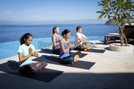 yoga group exercising at ocean front