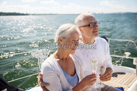 senior, couple, drinking, champagne, on, sail - 20174661