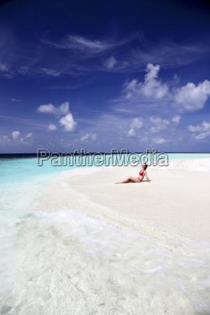 maldives woman sitting on beach at
