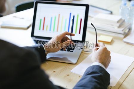 businessman studying bar chart on laptop