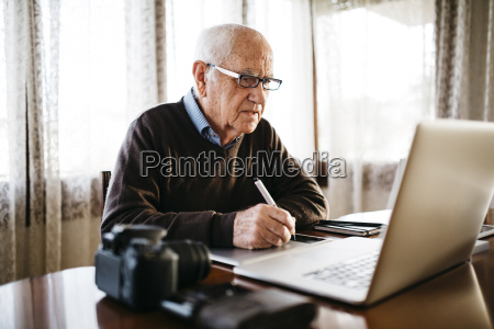 senior photographer working with laptop at