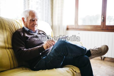 senior man sitting on couch using
