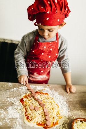 little boy preparing pizza at home