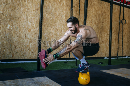 man keeping balance on a kettlebell