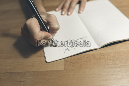 woman writing in notebook with a