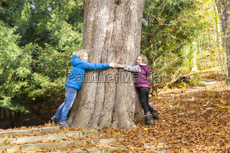 two children hugging tree in autumn