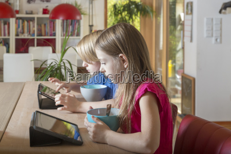 boy and girl using tablets at